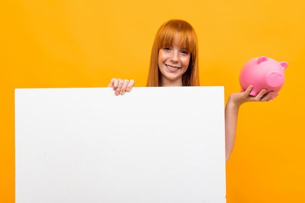 Menina sorridente segurando um cofrinho e um banner nas mãos