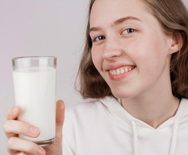 Menina sorridente, segurando um copo de leite fresco