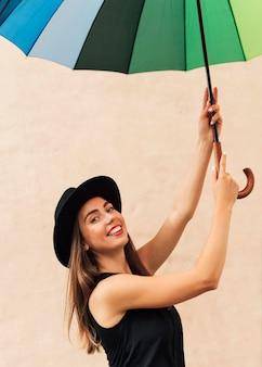 Menina sorridente segurando um guarda-chuva arco-íris