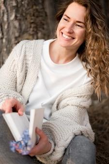 Menina sorridente, segurando um livro na floresta