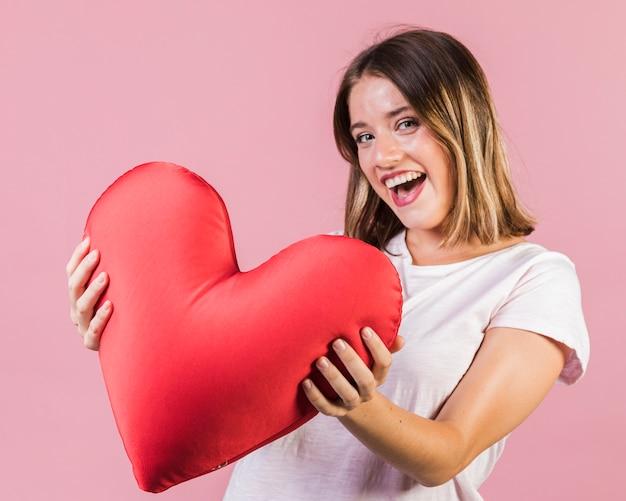 Menina sorridente segurando um travesseiro em forma de coração