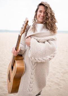 Menina sorridente segurando um violão na praia