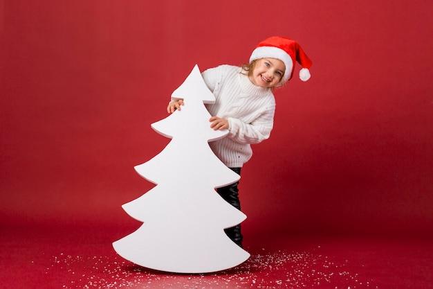 Menina sorridente segurando uma árvore artificial branca