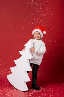 Menina sorridente segurando uma árvore branca artificial enquanto nevava