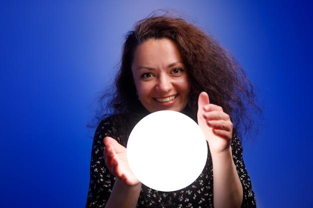 Menina sorridente segurando uma bola brilhante nas mãos. parede azul.