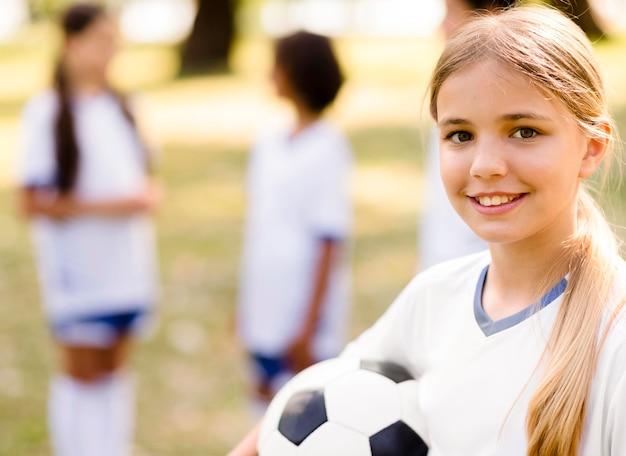 Menina sorridente segurando uma bola de futebol