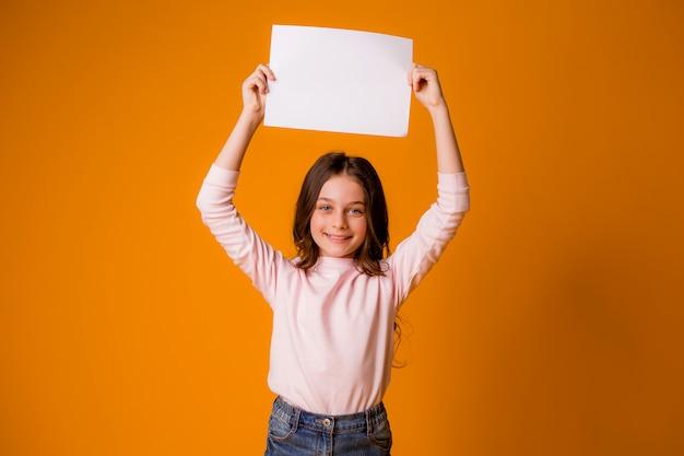 Menina sorridente segurando uma folha em branco sobre um fundo amarelo