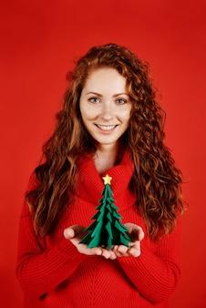 Menina sorridente segurando uma pequena árvore de natal