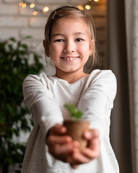 Menina sorridente segurando uma planta no vaso em casa