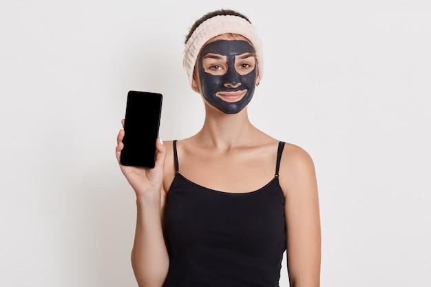 Menina sorridente, sendo fotografada após o banho, vestindo preto t shier e faixa de cabelo, isolada sobre a parede branca, mostrando o telefone inteligente com tela em branco.