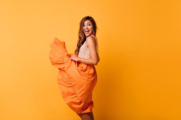Menina sorridente sensual brincando com sua saia laranja de verão. foto interna do feliz modelo feminino desfrutando de retratos.