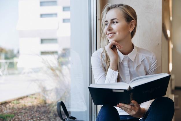 Menina sorridente senta com um livro no peitoril da janela