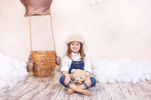 Menina sorridente senta-se no chão e segura um ursinho de pelúcia. menina brinca em um quarto de criança com um brinquedo.
