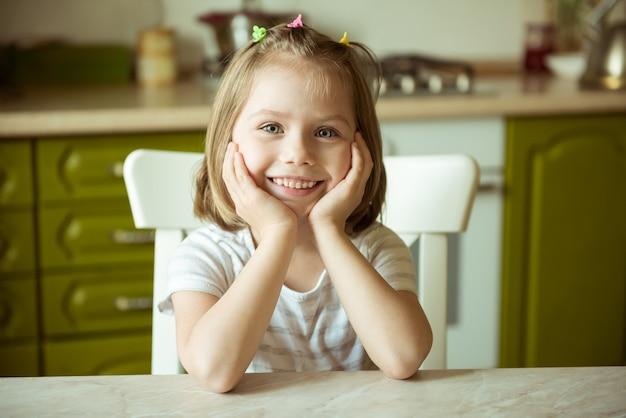 Menina sorridente sentada à mesa com as mãos na cabeça