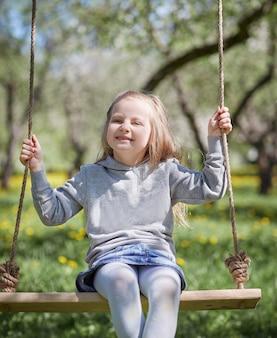 Menina sorridente sentada em um balanço no jardim. o conceito de felicidade infantil