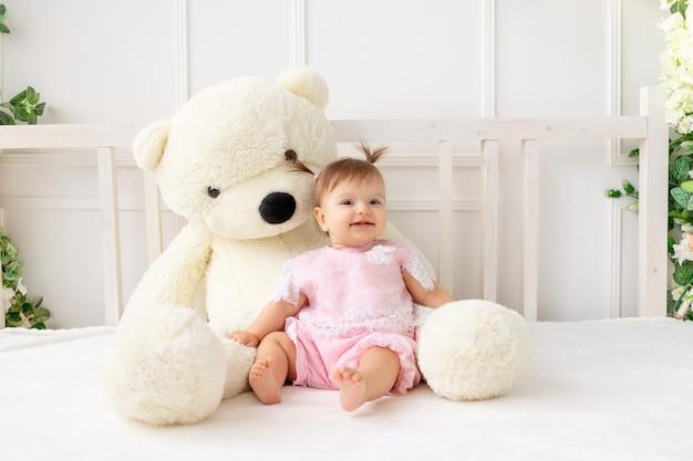 Menina sorridente sentada na cama com o ursinho de pelúcia