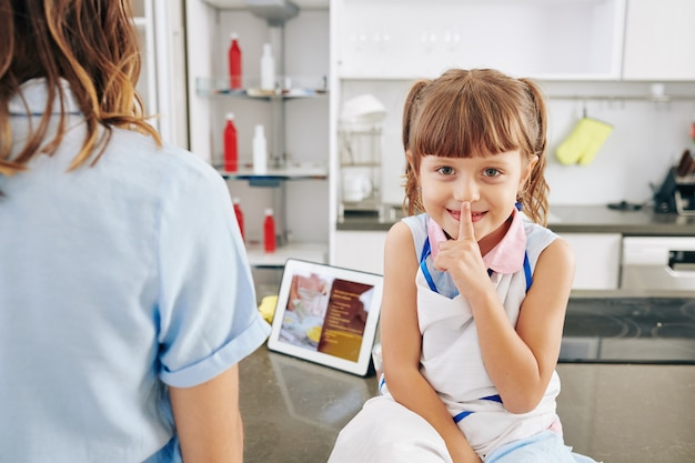 Menina sorridente sentada no balcão da cozinha e fazendo gesto de silêncio quando a mãe está preparando o jantar