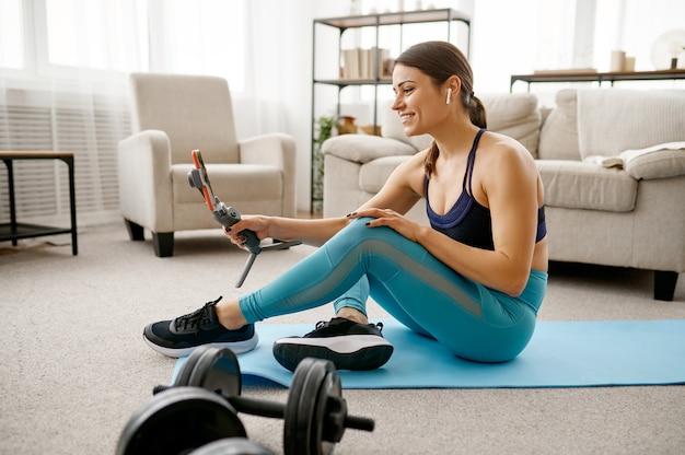 Menina sorridente sentada no chão em casa, treinamento físico online no laptop