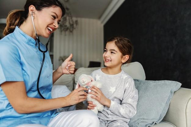 Menina sorridente, sentada no sofá e segurando seu coelhinho de brinquedo. médico tentando relaxar a garota, então ela está fingindo examinar seu coelhinho com o estetoscópio. bunny está saudável.