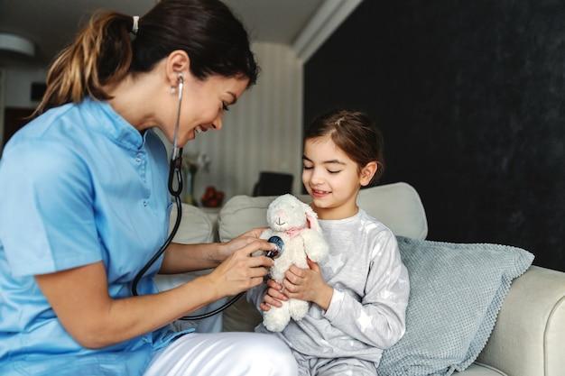 Menina sorridente, sentada no sofá e segurando seu coelhinho de brinquedo. médico tentando relaxar a garota, então ela está fingindo examinar seu coelhinho com o estetoscópio.