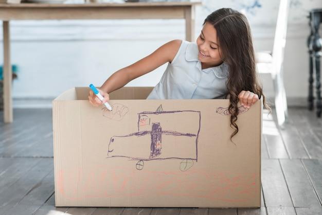 Menina sorridente sentado dentro da caixa de papelão de desenho com marcador