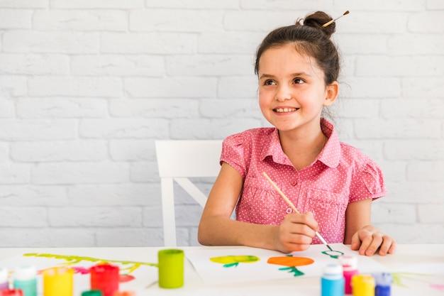 Menina sorridente, sentado na cadeira de pintura em papel branco com pincel