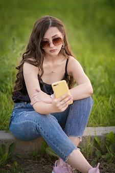 Menina sorridente sentado na grama do parque e escreve uma mensagem no telefone