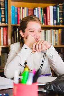 Menina sorridente, sentando, com, caderno, em, biblioteca