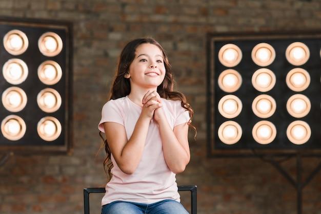 Menina sorridente, sentando, contra, fase, luz, aplaudindo, dela, mãos