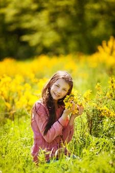 Menina sorridente, sentando, em, a, campo, de, primavera, amarelo floresce