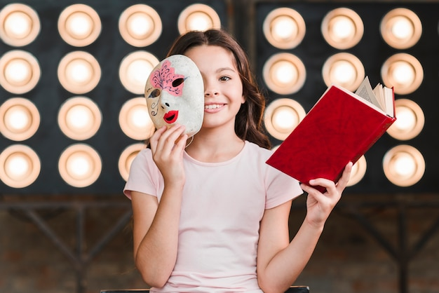 Menina sorridente, sentando, frente, luz fase, segurando máscara, e, livro