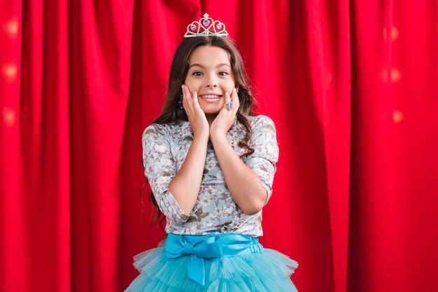 Menina sorridente surpresa em frente a cortina vermelha
