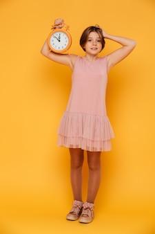 Menina sorridente surpresa, mostrando o despertador e segurando sua cabeça isolada