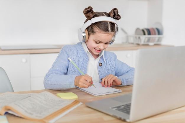 Menina sorridente, tendo uma aula on-line