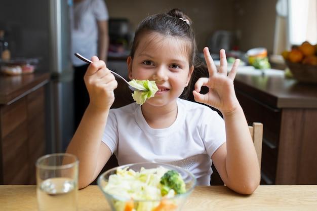 Menina sorridente, tendo uma refeição saudável