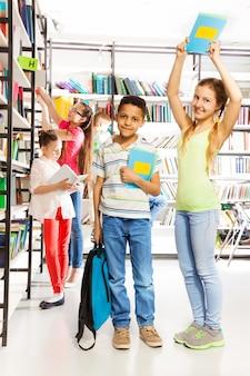 Menina sorridente tenta acertar menino com livro na biblioteca