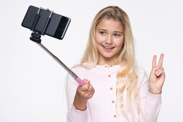 Menina sorridente tirando selfies de si mesma