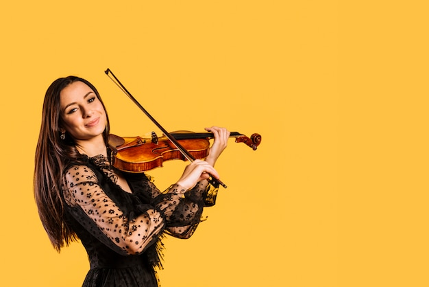 Menina sorridente tocando violino