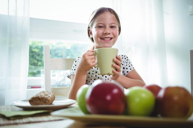 Menina sorridente tomando café