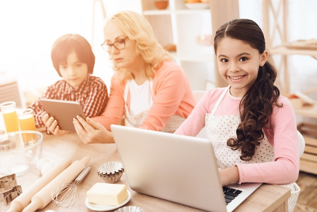 Menina sorridente, usando computador portátil, em, cozer cozinha, conceito