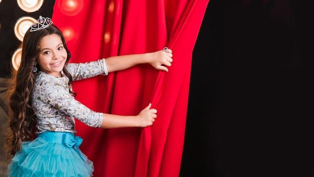 Menina sorridente usando coroa abrindo a cortina vermelha
