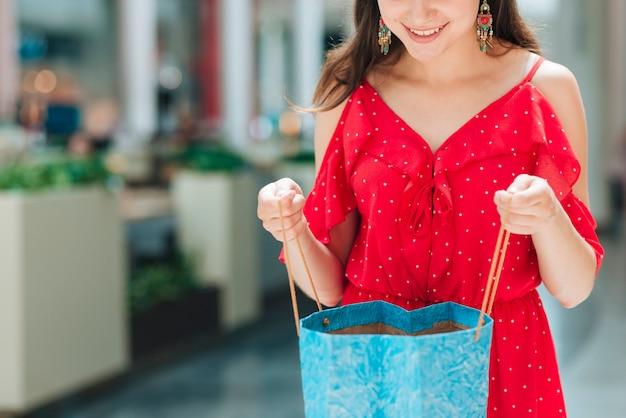 Menina sorridente, verificando o saco de compras