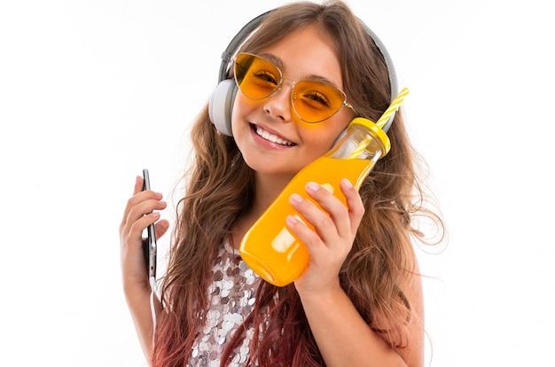 Menina sorridente, vestido brilhante e óculos de sol amarelos brilhantes, com grandes fones de ouvido brancos, ouvindo música e segurando o smartphone fino e garrafa com suco de laranja isolado