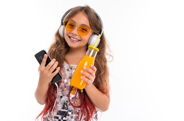 Menina sorridente, vestido brilhante e óculos de sol amarelos brilhantes, com grandes fones de ouvido brancos, ouvindo música e segurando preto smartphone e garrafa com suco de laranja isolado