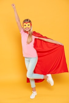 Menina sorridente, vestindo fantasia de super-herói
