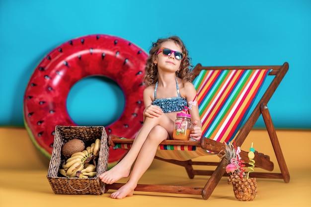 Menina sorridente, vestindo maiô e óculos de sol, segurando o frasco com suco ou coquetel com canudos coloridos, sentado na espreguiçadeira do arco-íris