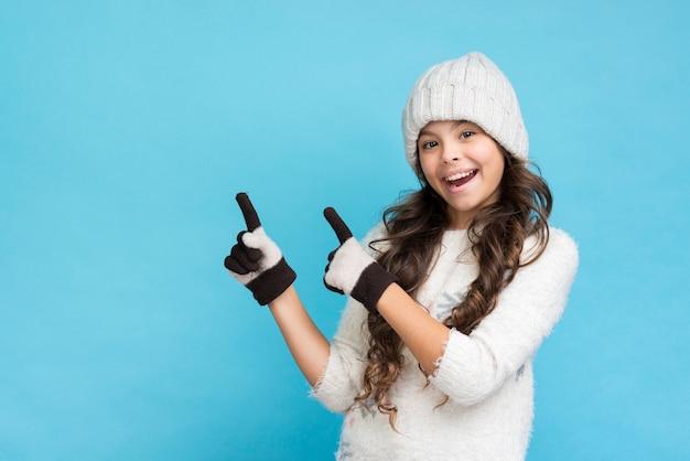 Menina sorridente, vestindo roupas de inverno, apontando