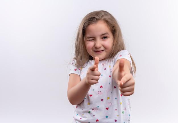 Menina sorridente, vestindo uma camiseta branca piscando e mostrando um gesto com as duas mãos sobre um fundo branco isolado