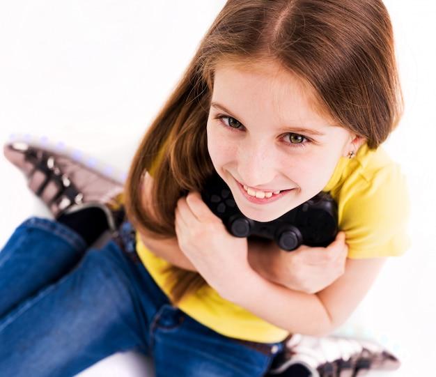 Menina sorrindo amplamente, usando o joystick, pronto para ganhar