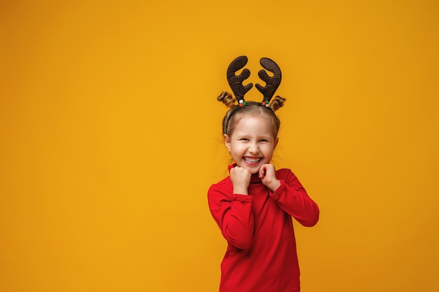 Menina sorrindo com chifres de rena na cabeça